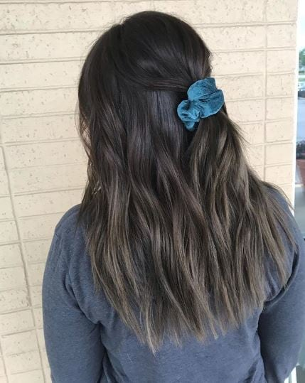 Woman with wavy long ash brown hair wearing a srunchie