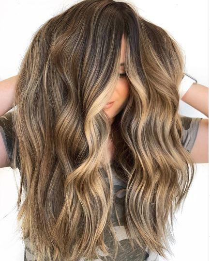 Woman with balayage highlights on long wavy hair