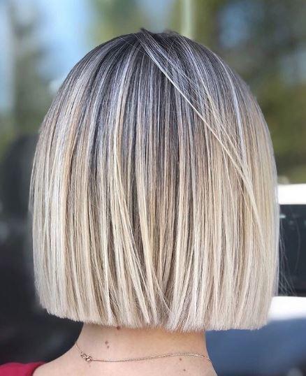 Woman with blonde balayage on straight bob