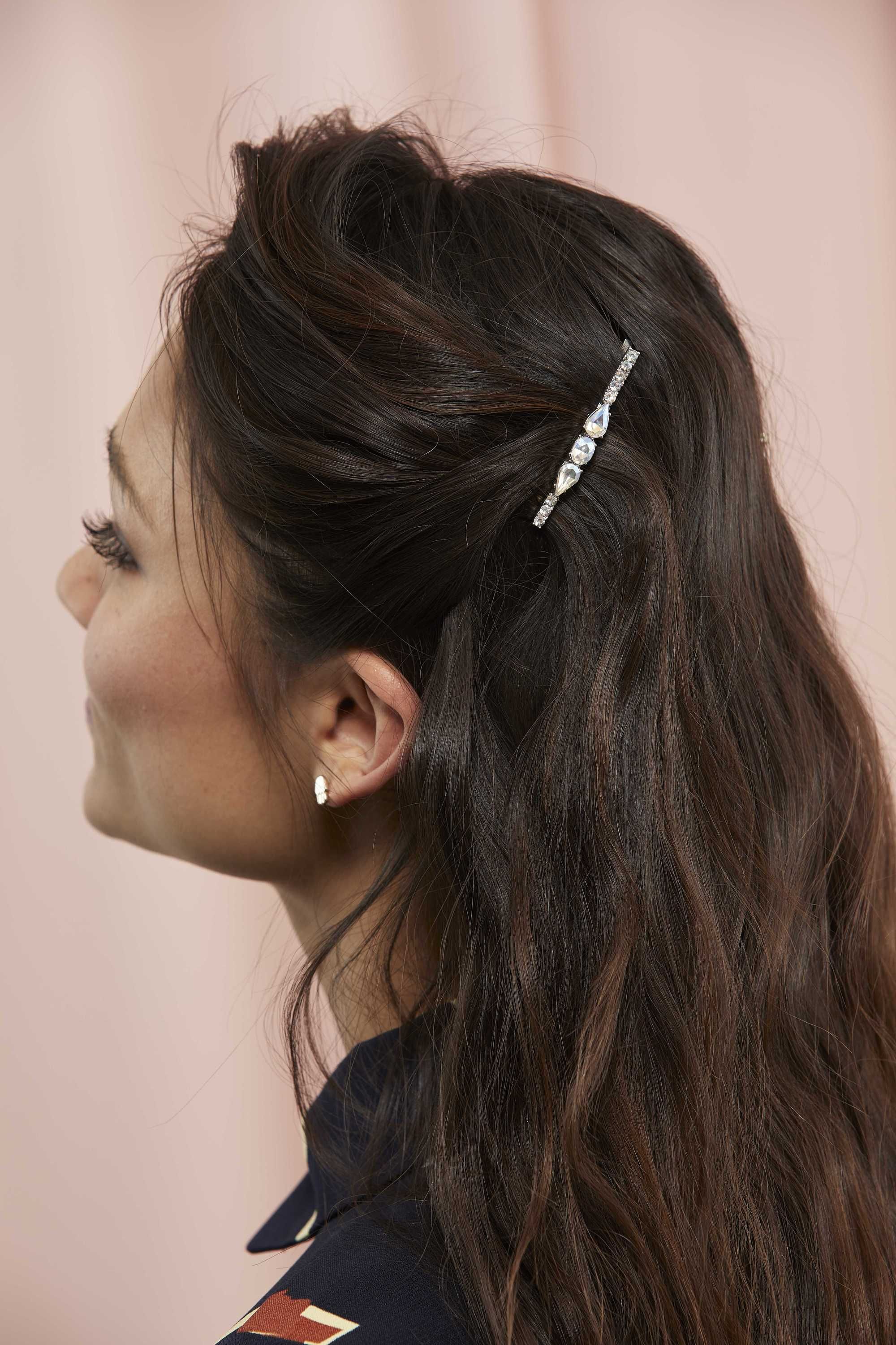 Woman with long dark brown wavy hair with a barrette hair pin