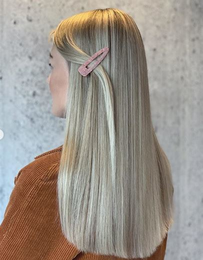 Woman with long straight blonde balayage hair