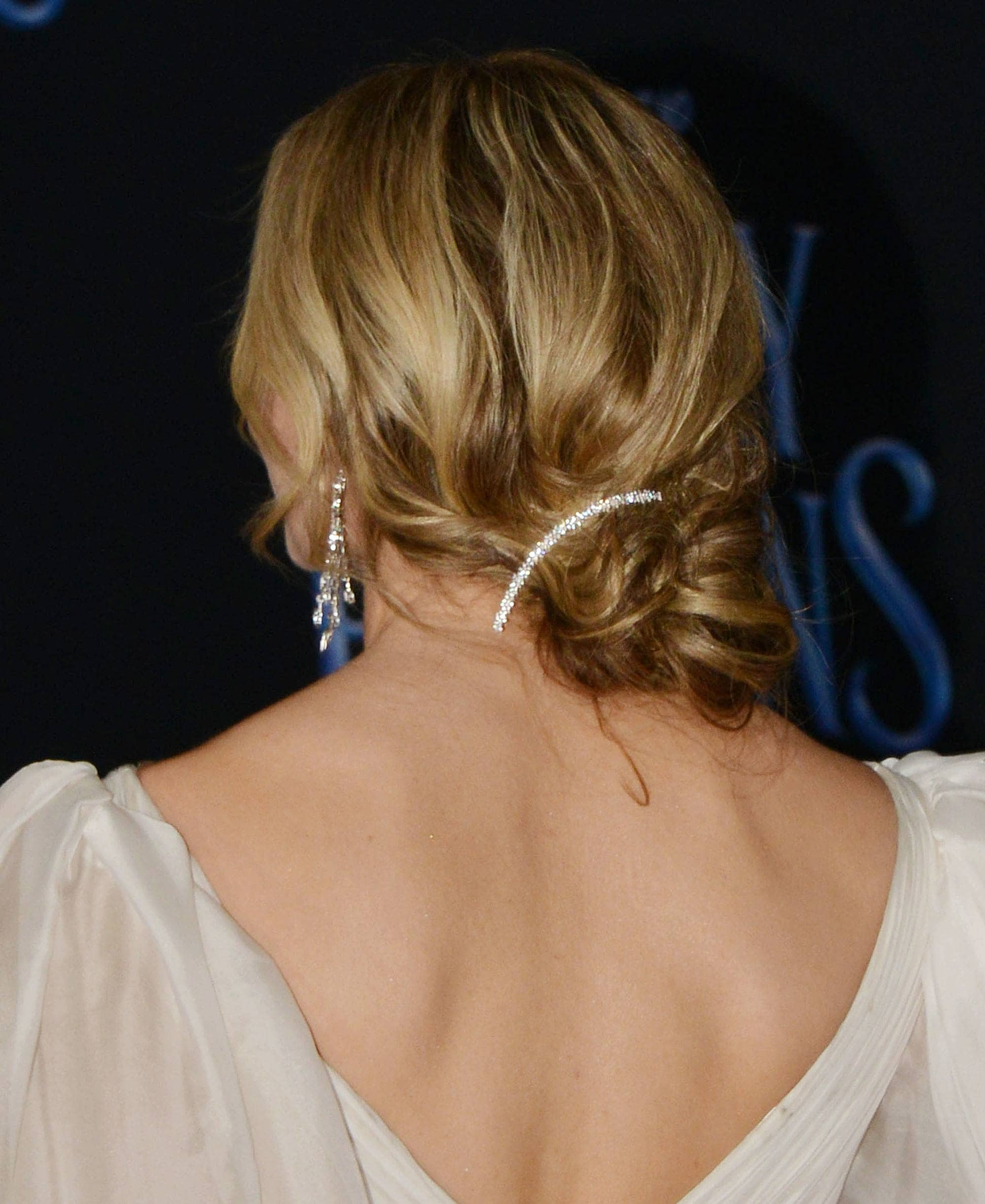 Woman with messy bronde hair styled into a low chignon with hair pin