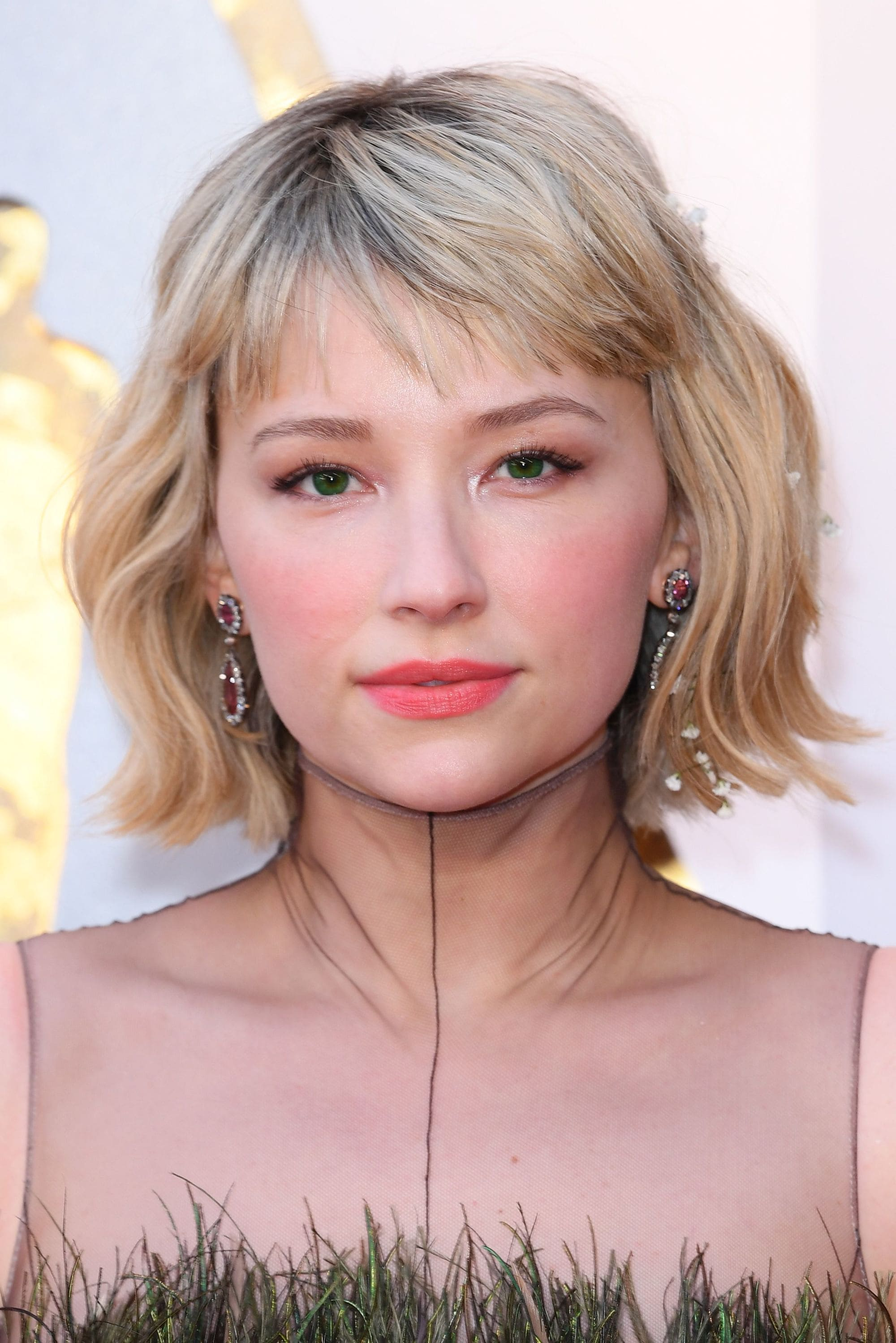 Hailey Bennett with a blonde wavy bob with bangs