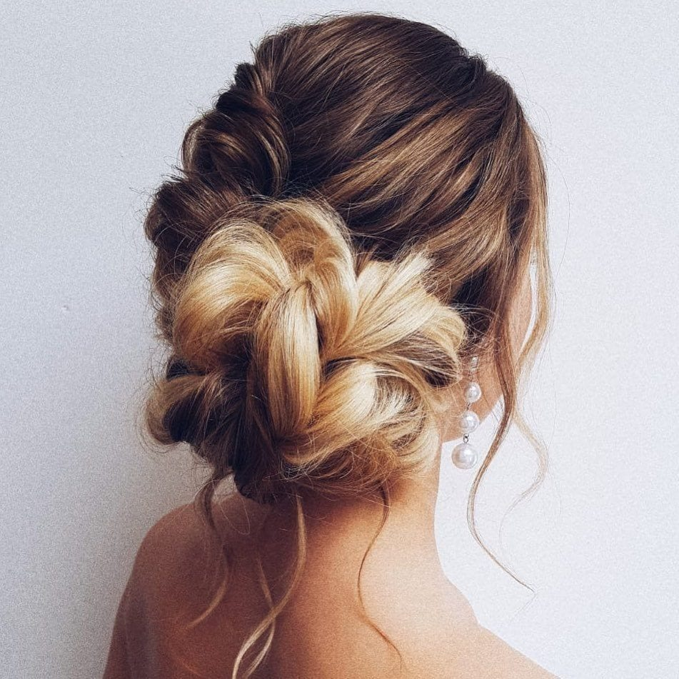woman with blonde and brown hair styled into a braided side bun