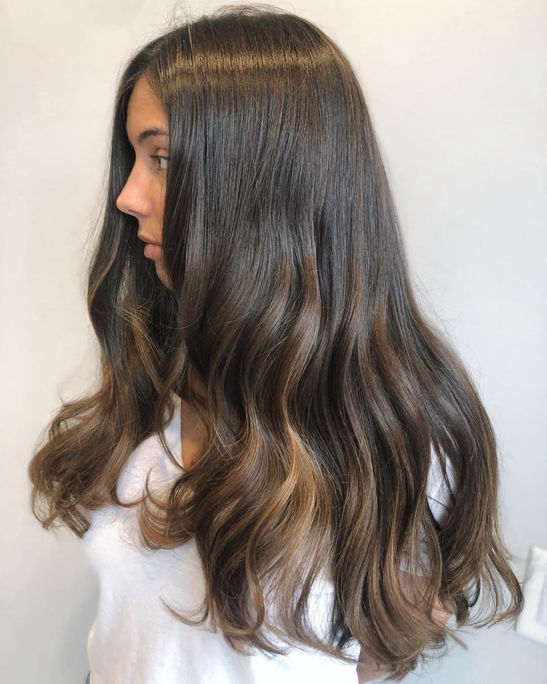 Woman with long wavy dark brunette balayage hair