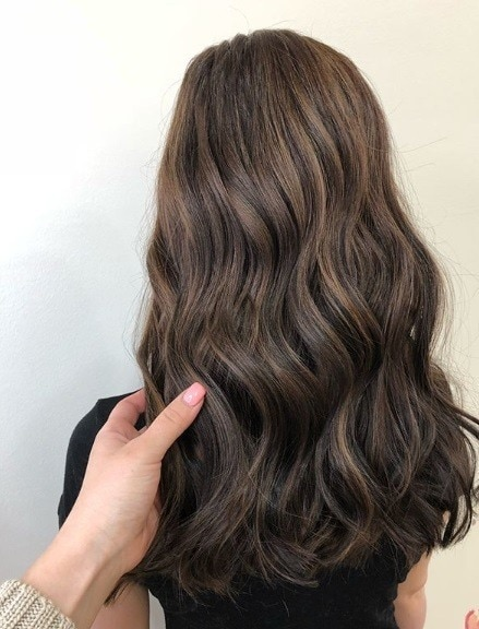 Woman with long wavy brunette hair with dark lowlights