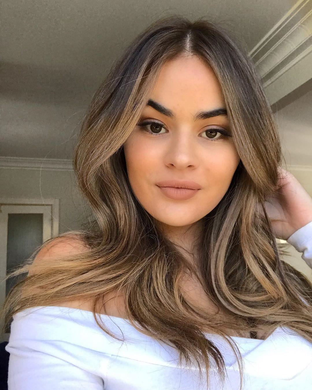 Woman with bronde balayage hair with face-framing highlights