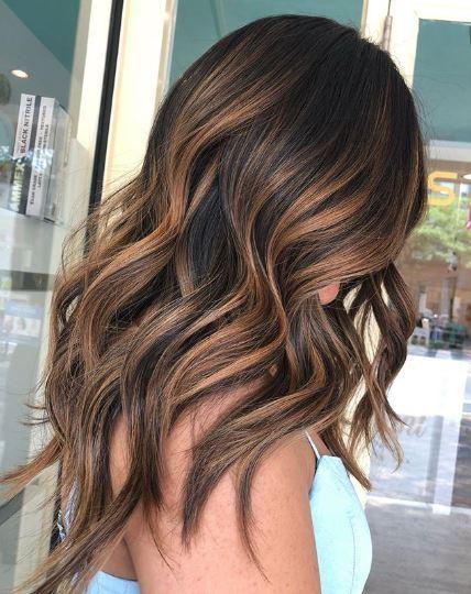 Woman with long wavy caramel balayage hair