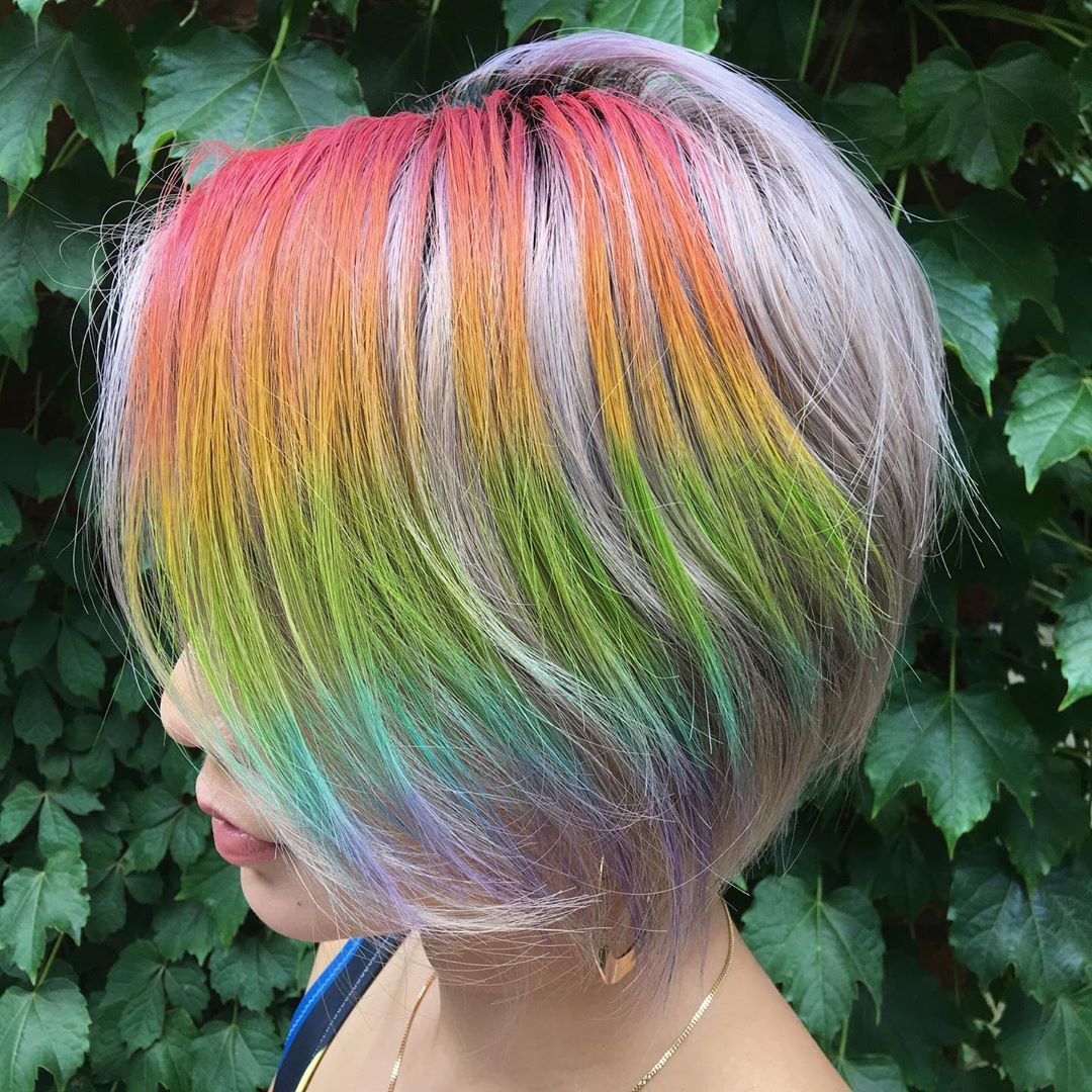 woman with silver hair with rainbow hair chalk in it