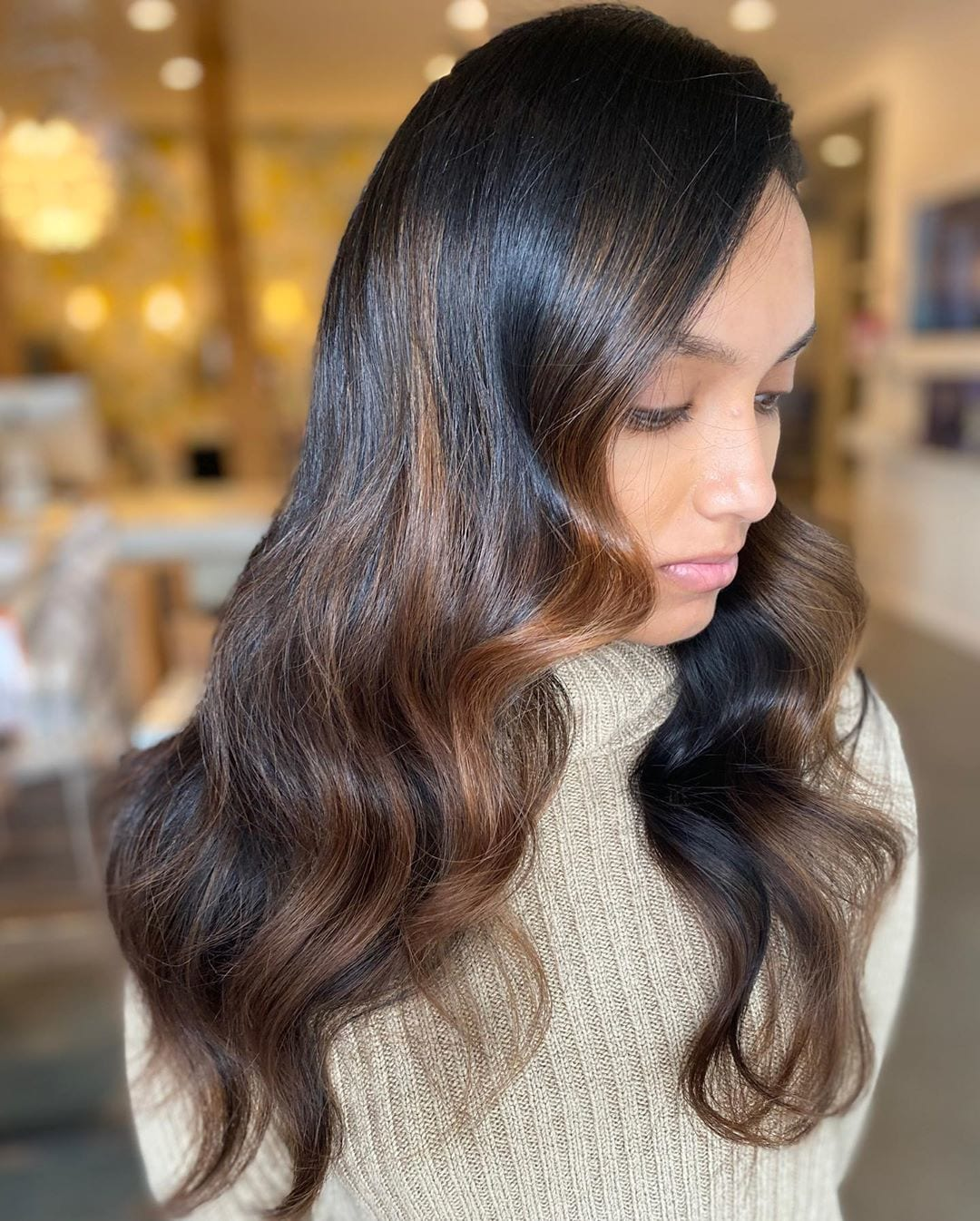 Woman with long dark wavy brunette copper balayage hair
