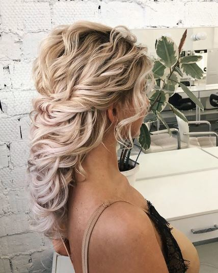 Curly blonde hair in loose pinned braid