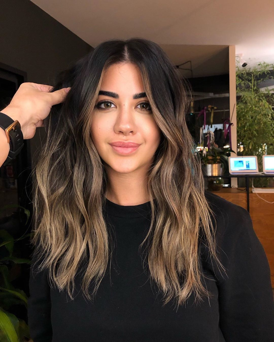 Woman with dark brunette hair with light ash brown balayage