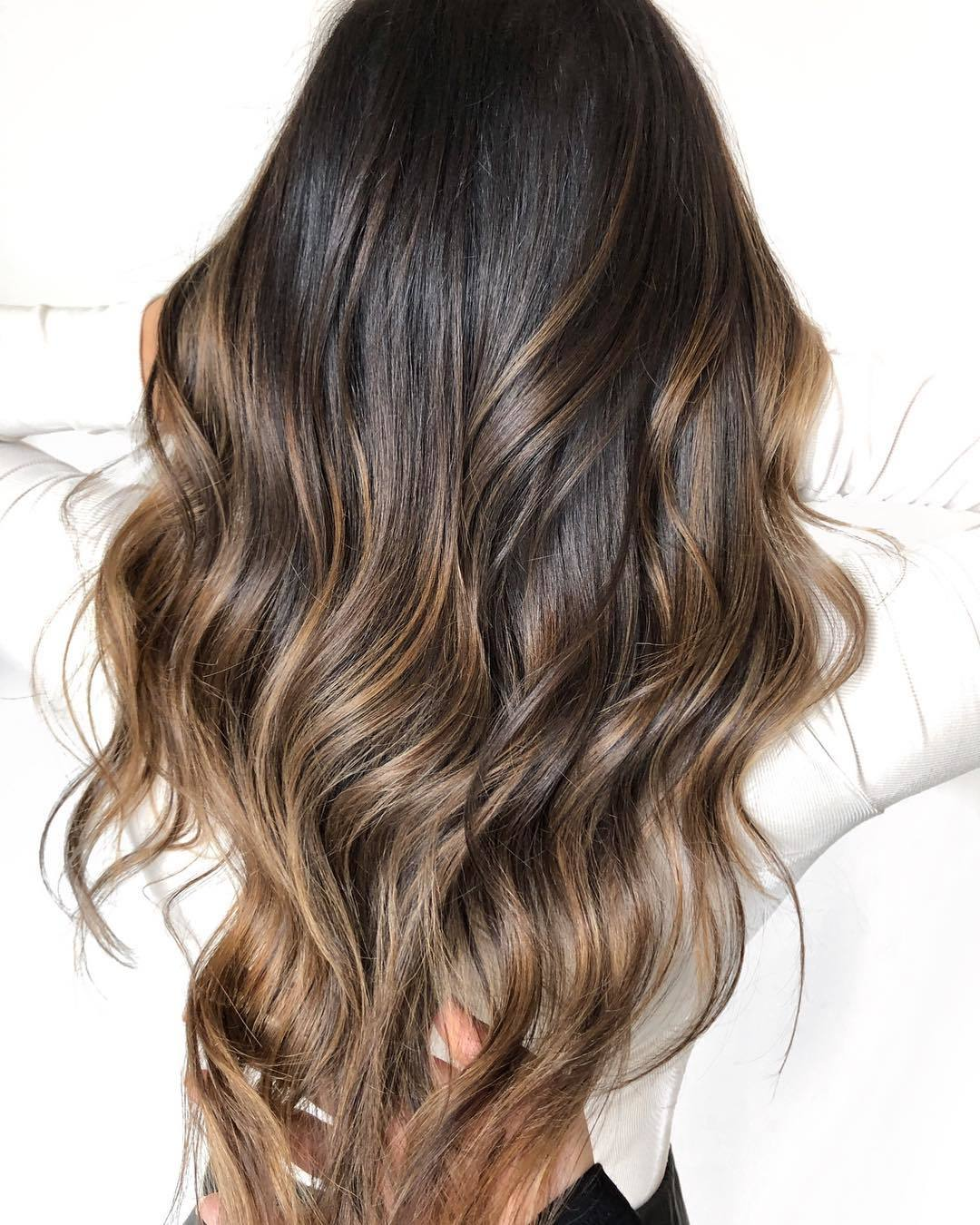woman with long dark brown hair with caramel highlights