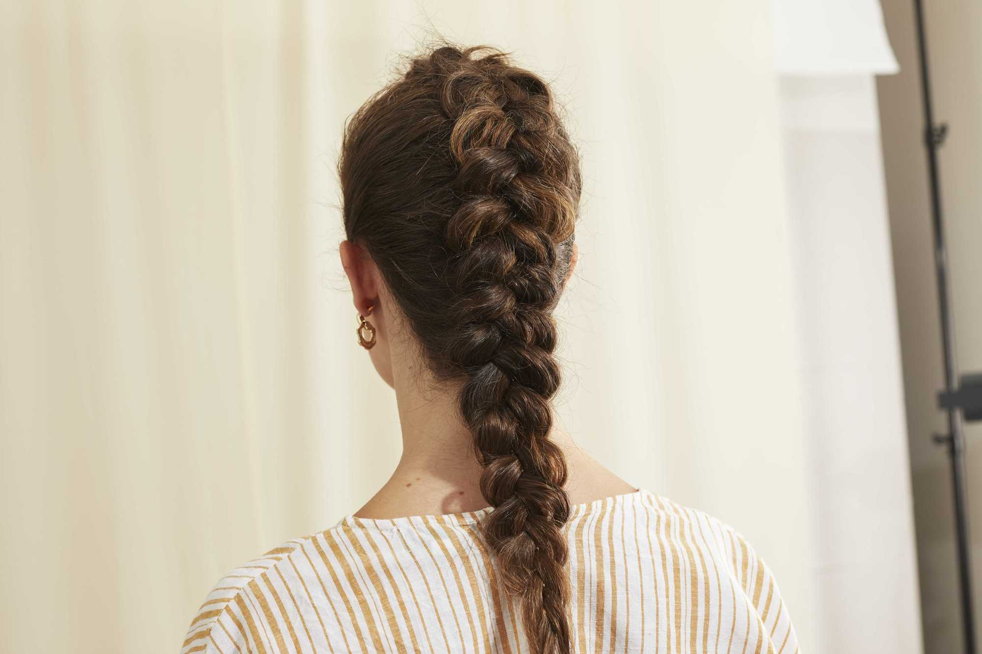Woman with long brunette hair in a Dutch braid