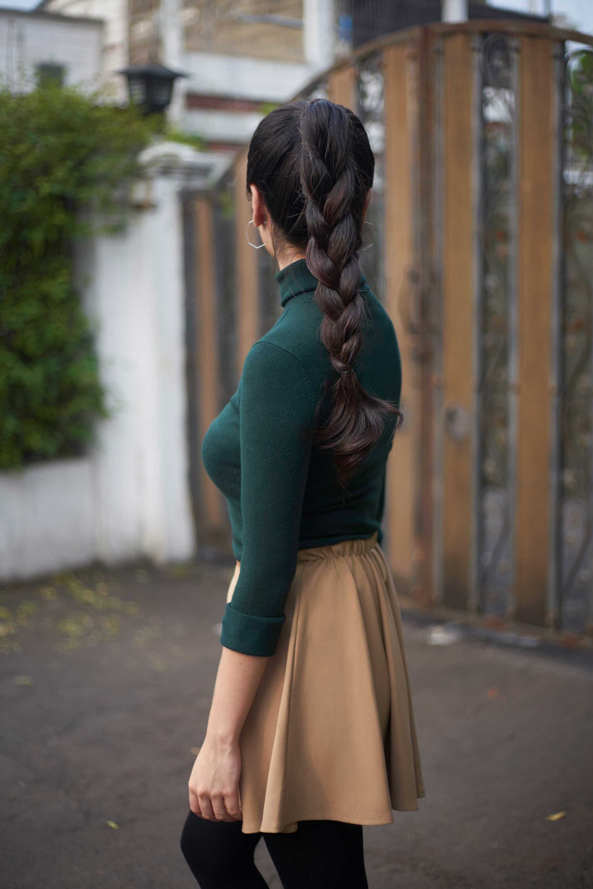 woman with ;pong dark brown braided ponytail