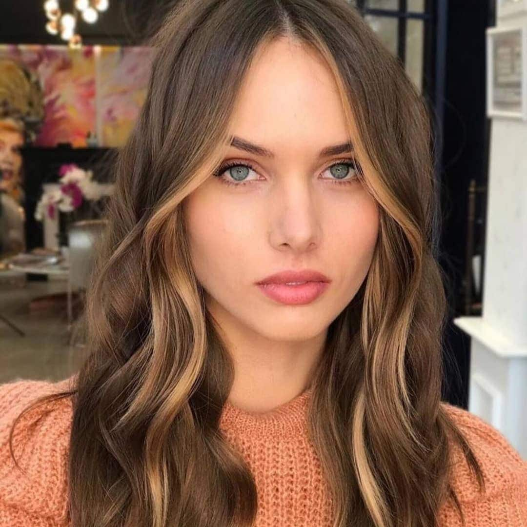 Woman with brunette wavy hair with blonde face framing highlights