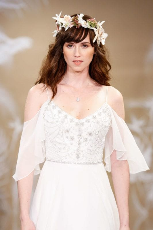 Model on the bridal runway with flower crown on her chestnut brown wavy hair with fringe