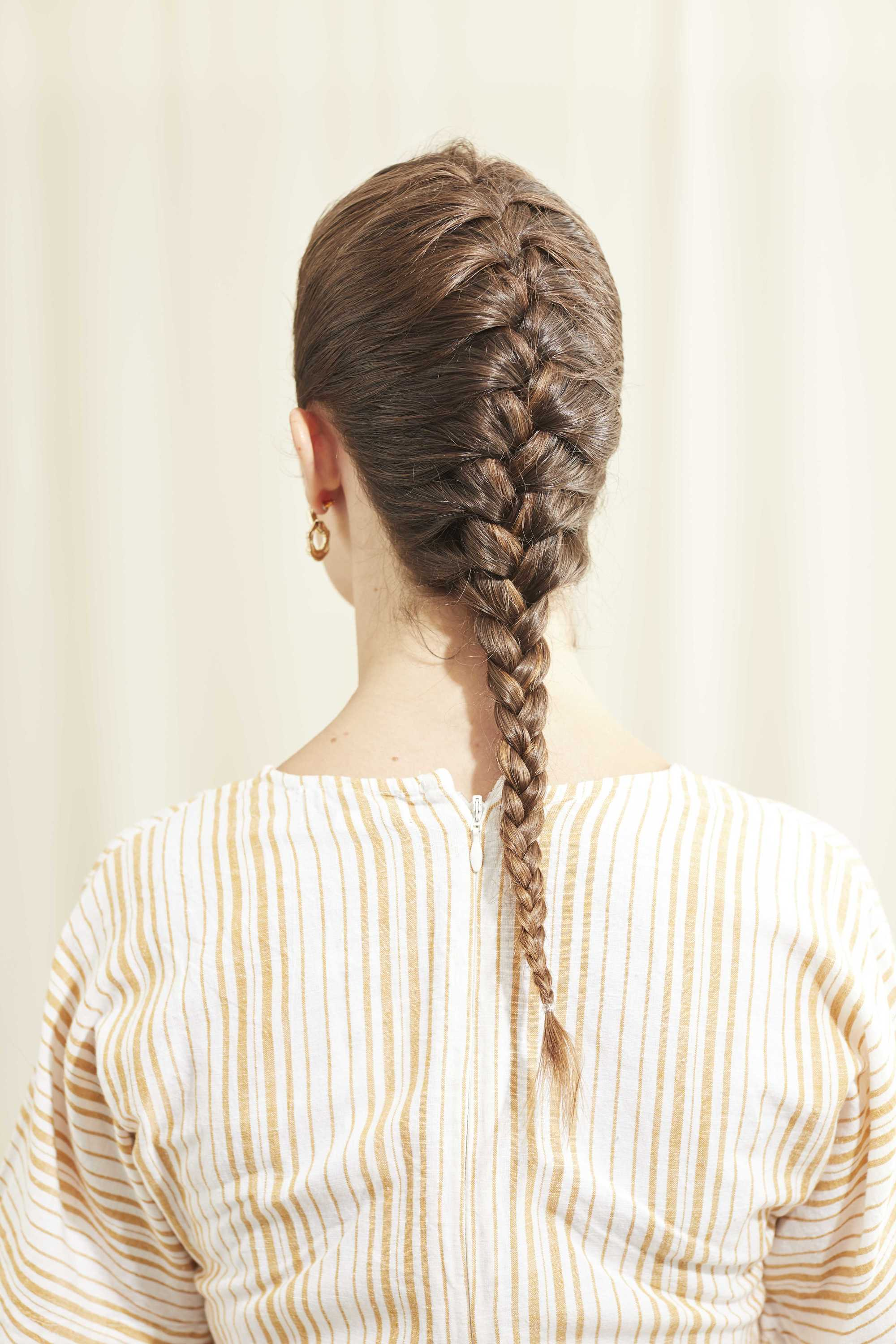 Woman with long brunette hair in a French braid