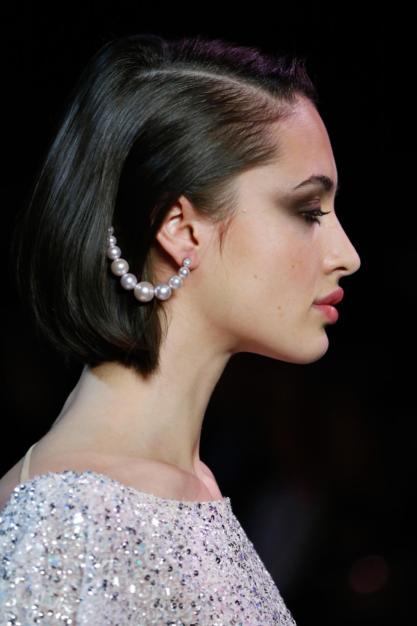 Woman with straight dark brown bob with pearl accessory