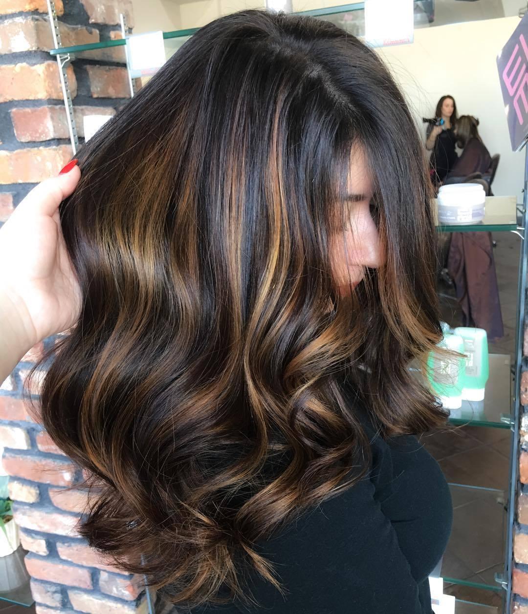 woman with dark brown hair and golden blonde hair streaks
