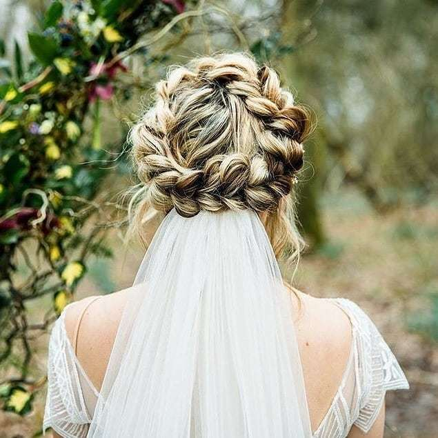 Woman with blonde hihlighted hair in halo braid with wedding veil