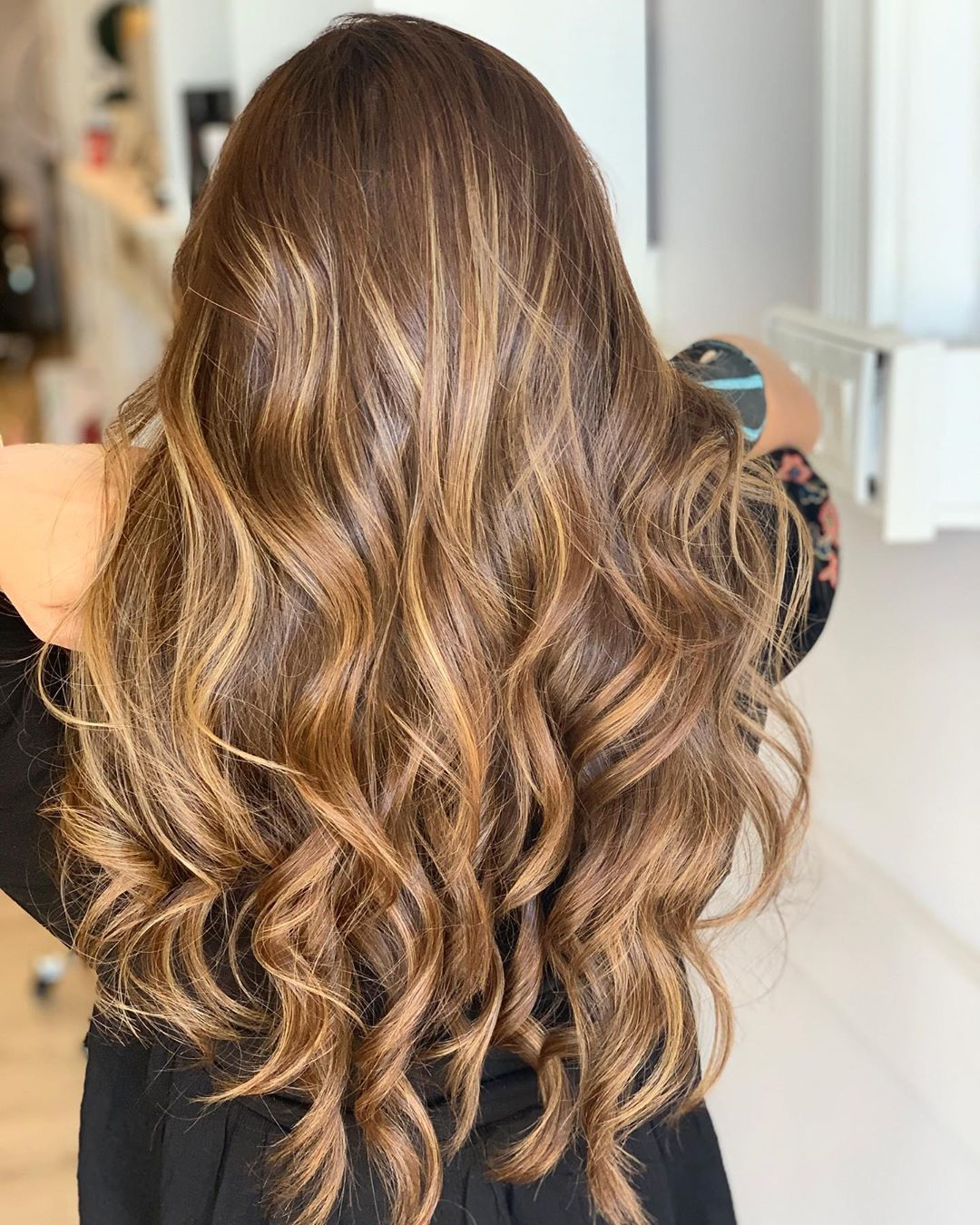 woman with long curly honey brown hair