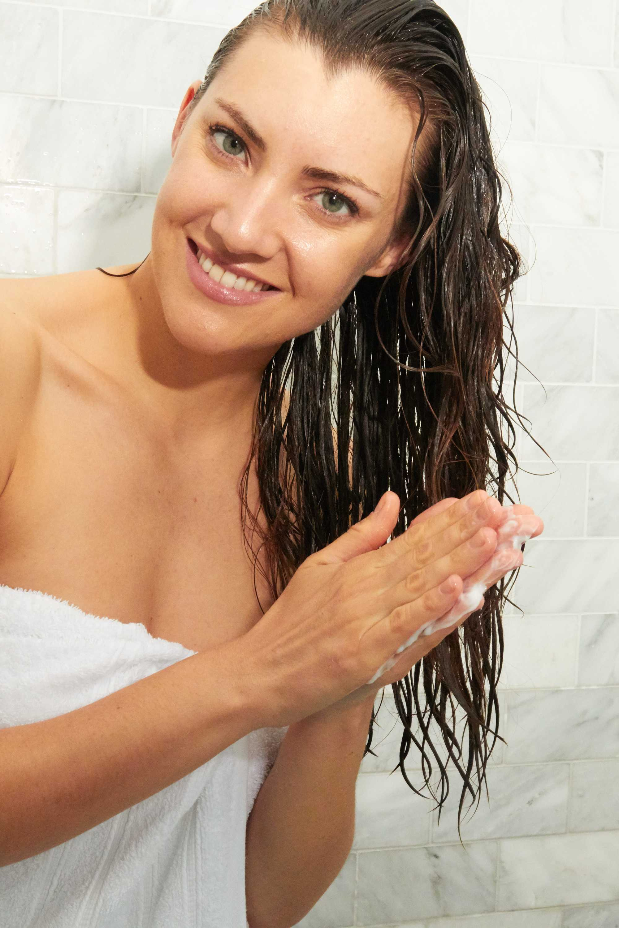 brunette woman smiling and putting shampoo onto her hair