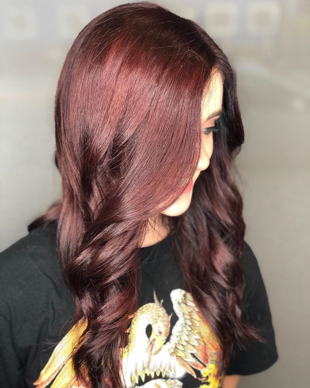 woman with long curly cherry cola hair