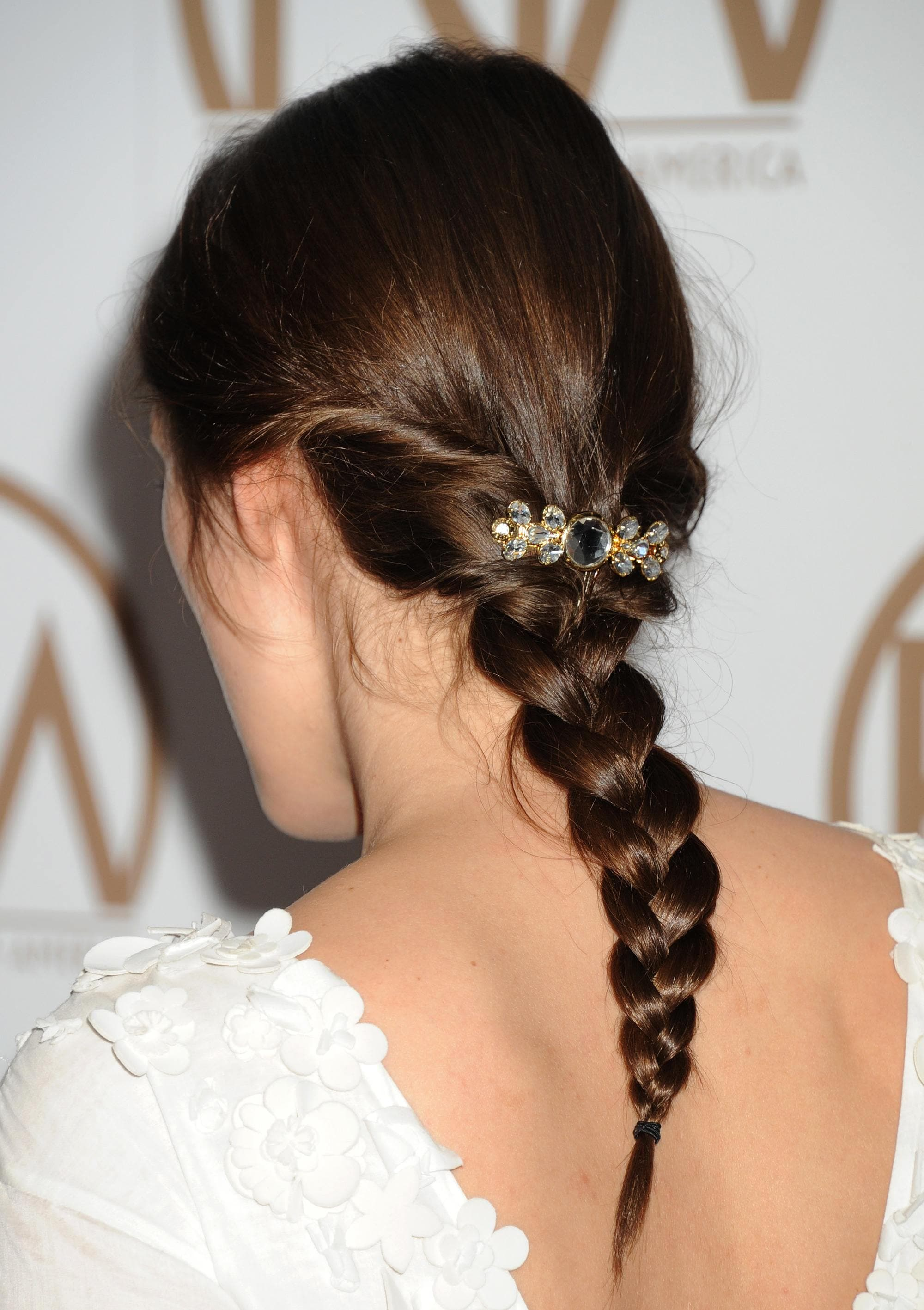 Woman with dark brown hair styled into a low braid with pins