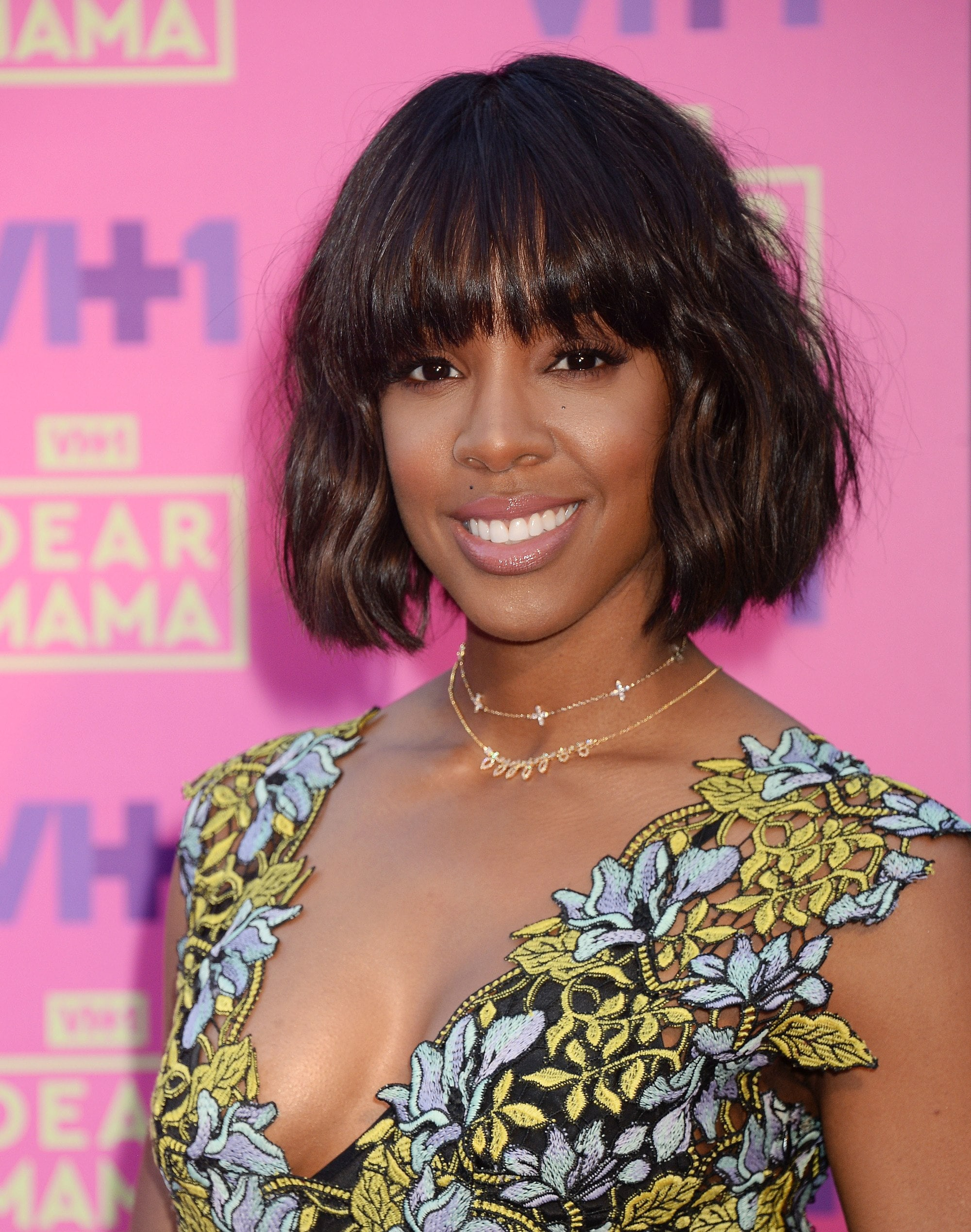 Kelly Rowland with a brunette wavy bob with bang