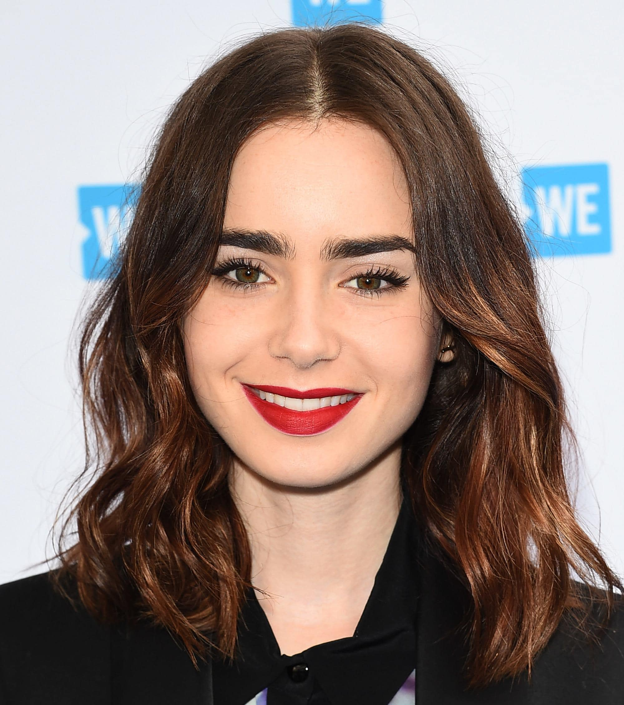 Lily Collins with a brunette wavy lob