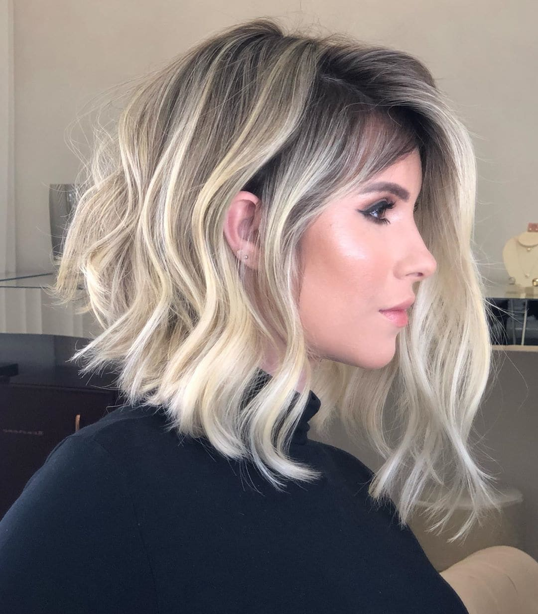 Woman with an ash blonde wavy inverted lob