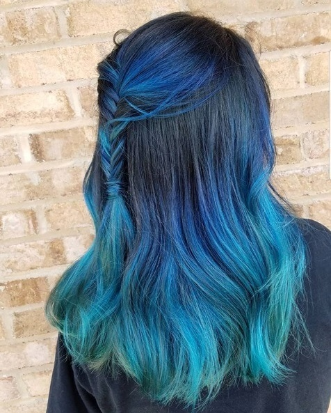 Woman with dark to light blue ombre mid-length hair in a half-up fishtail braid