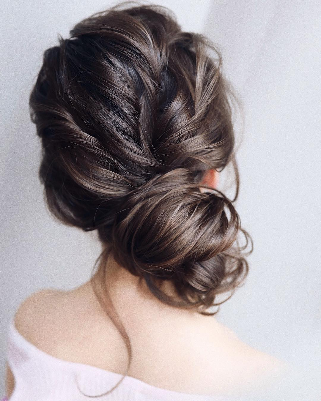 Woman with dark brown hair styled into a messy side bun
