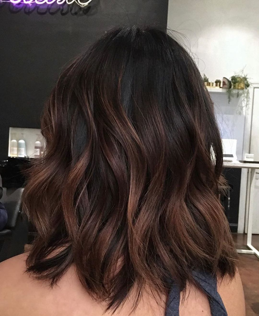Woman with a wavy chocolate brown balayage long bob