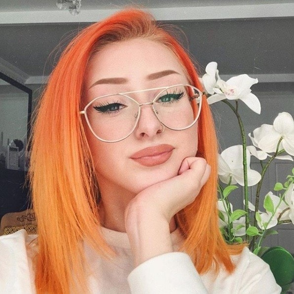 Woman with bright orange straight shoulder-length hair