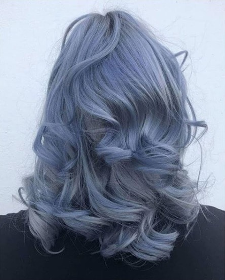 Woman with pastel blue shoulder length curly hair