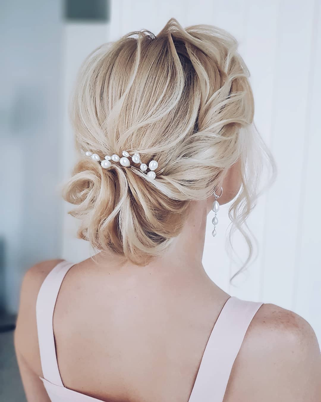Woman with blonde hair styled into a romantic low wavy bun with pearl pins