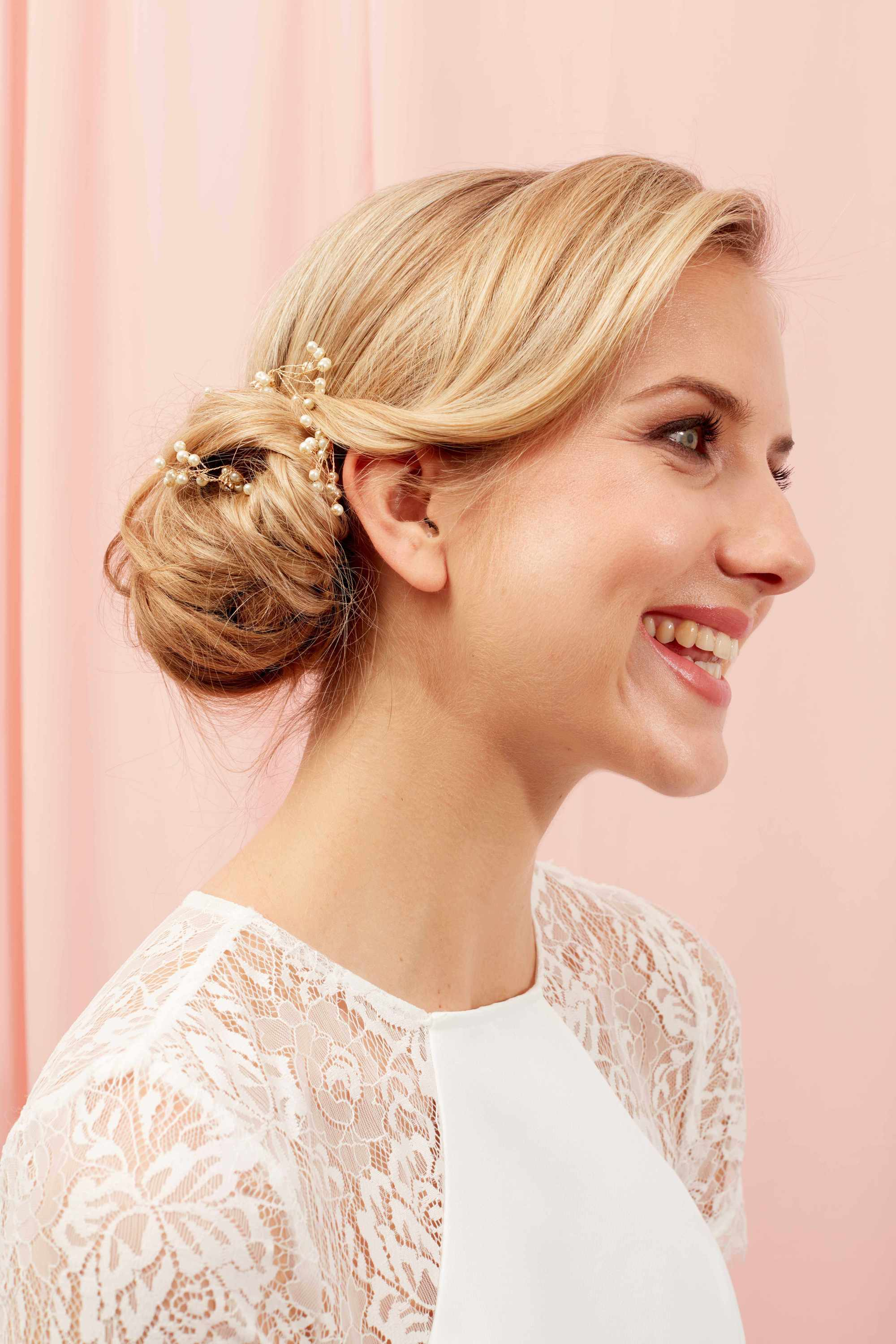 Bride with golden blonde hair styled into a low bun with pearls in it