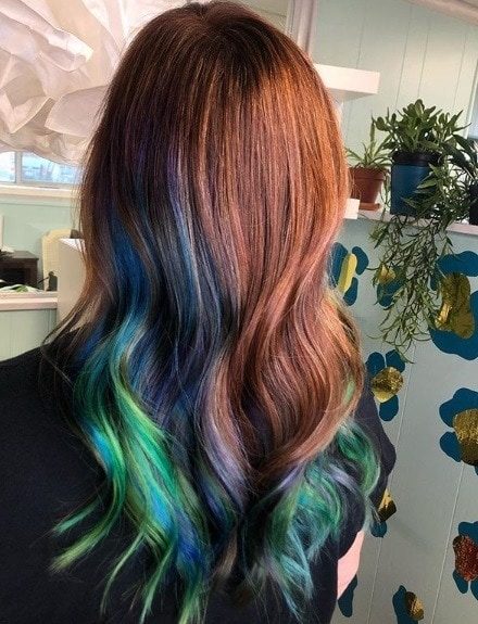 Woman with red wavy hair with blue and green peekaboo highlights