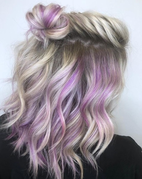 Woman with mid-length ash blonde hair with purple hidden highlights
