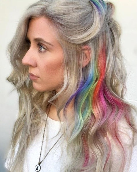 Woman with long wavy ash blonde hair with rainbow highlights