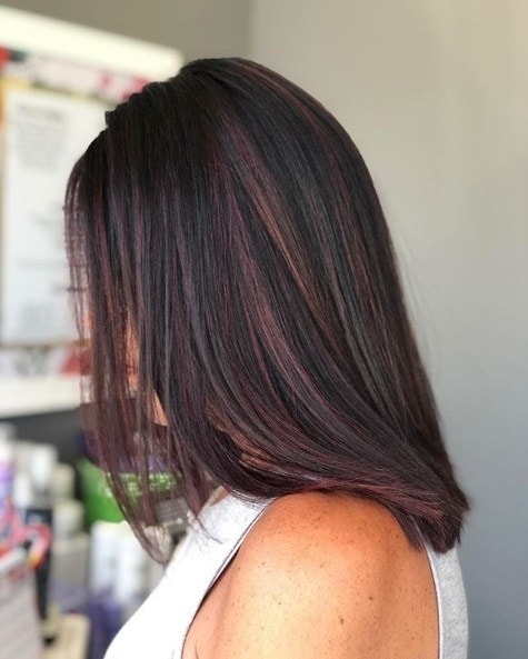 Woman with straight shoulder length dark brunette hair with red highlights