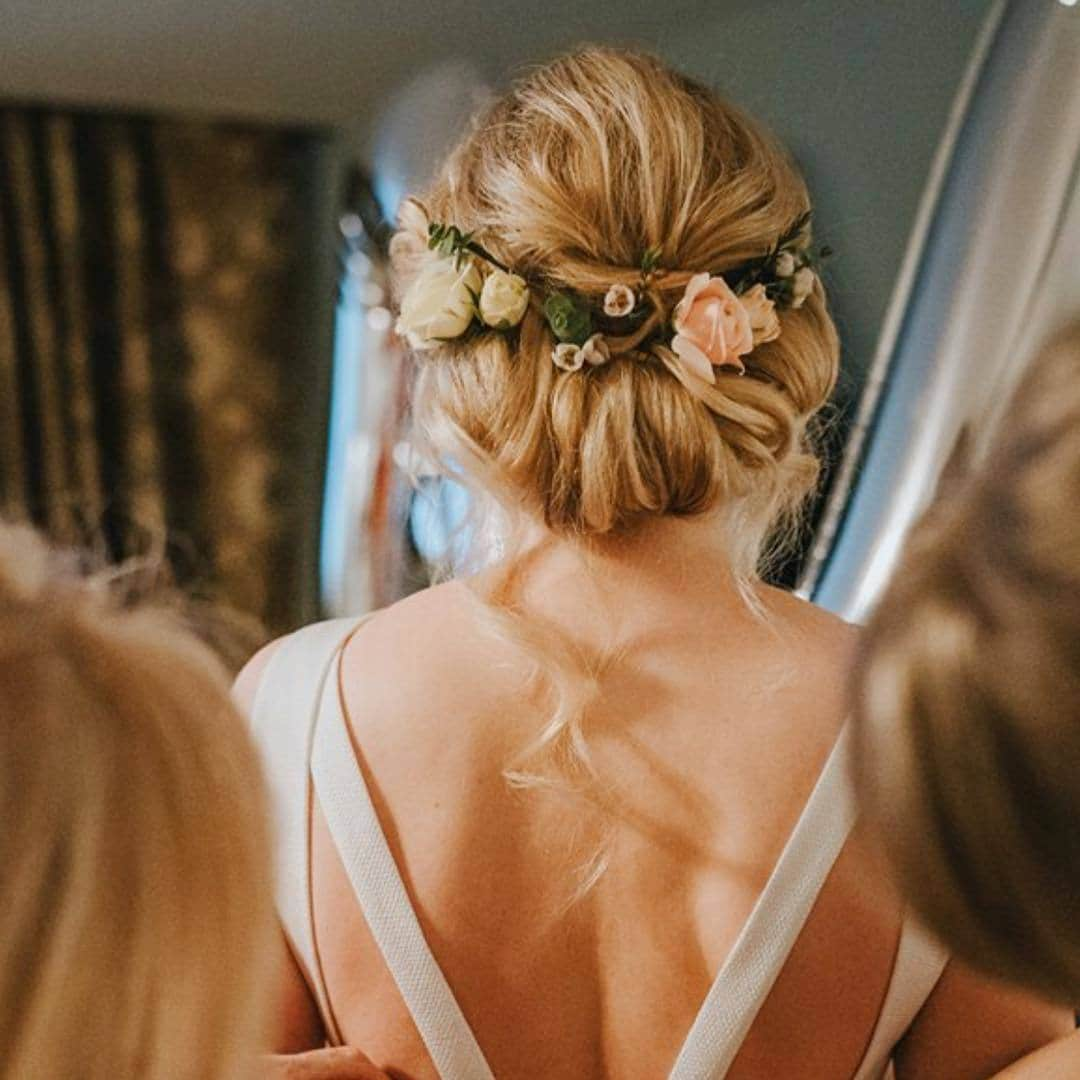 woman with dirty blonde hair styled into a floral tuck wedding hairstyle