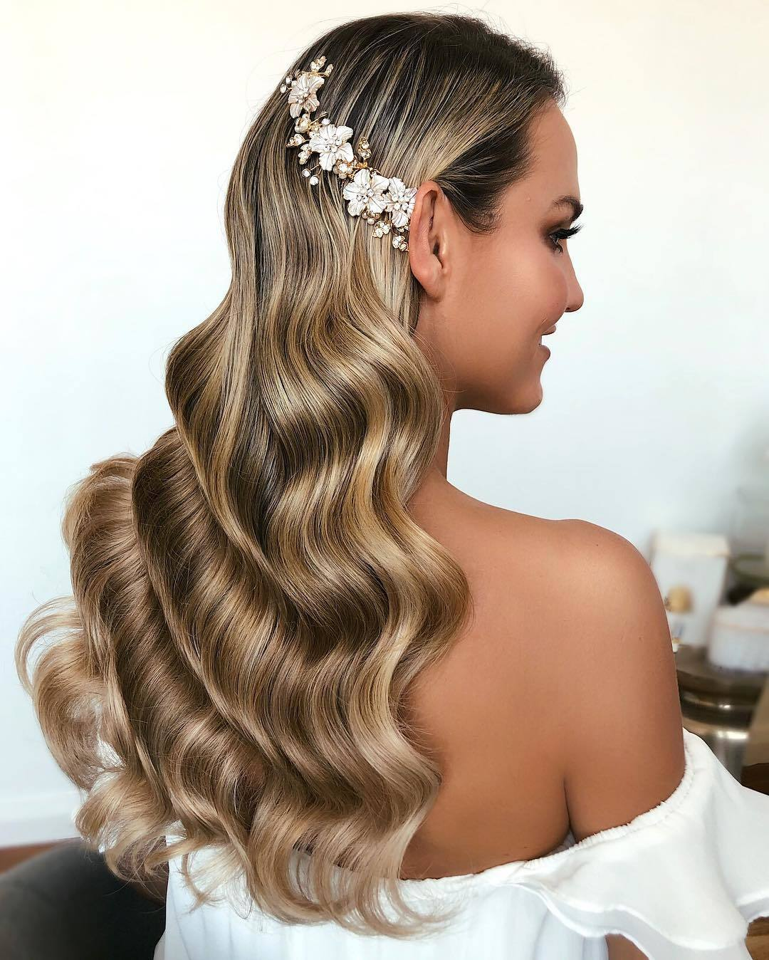 woman with long dark blonde hollywood waves with hair pins