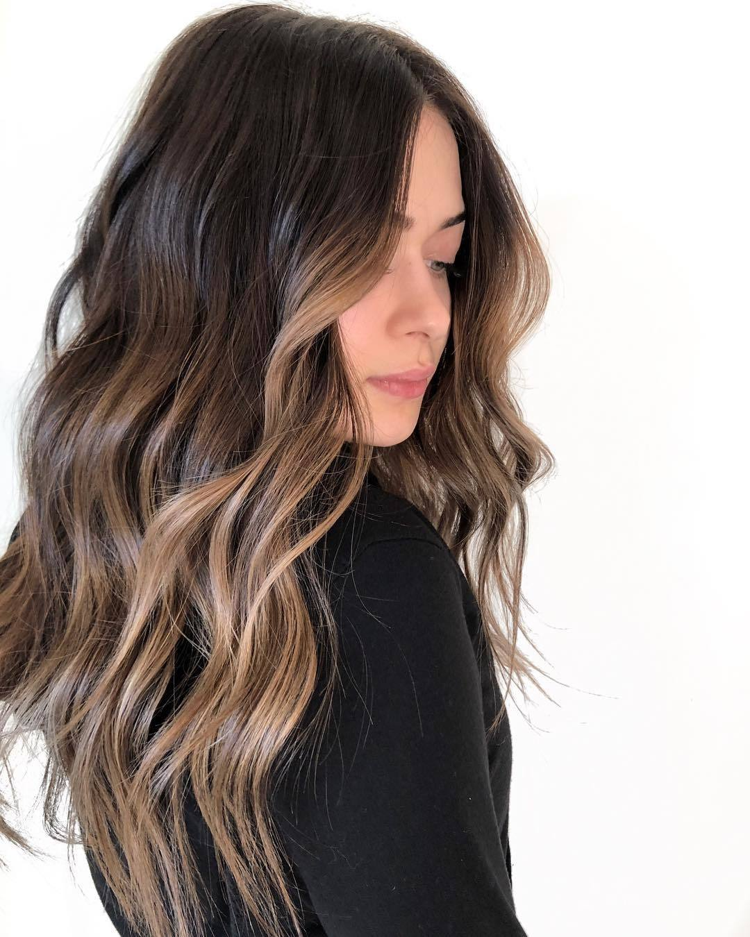 Woman with long wavy brunette hair with face framing balayage