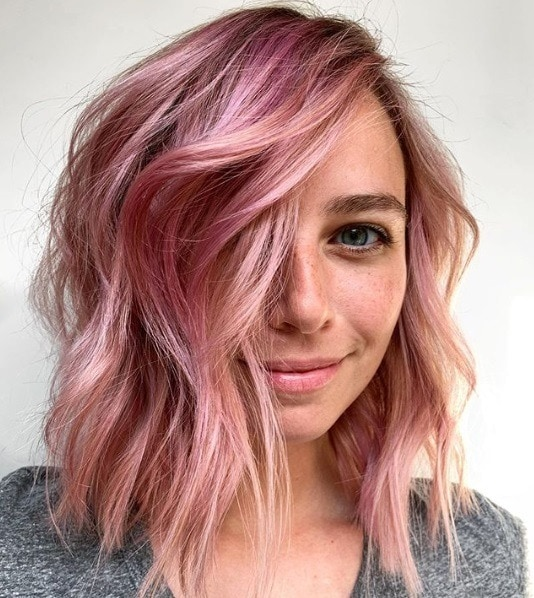 Woman with a rose gold wavy bob with sweeping bangs