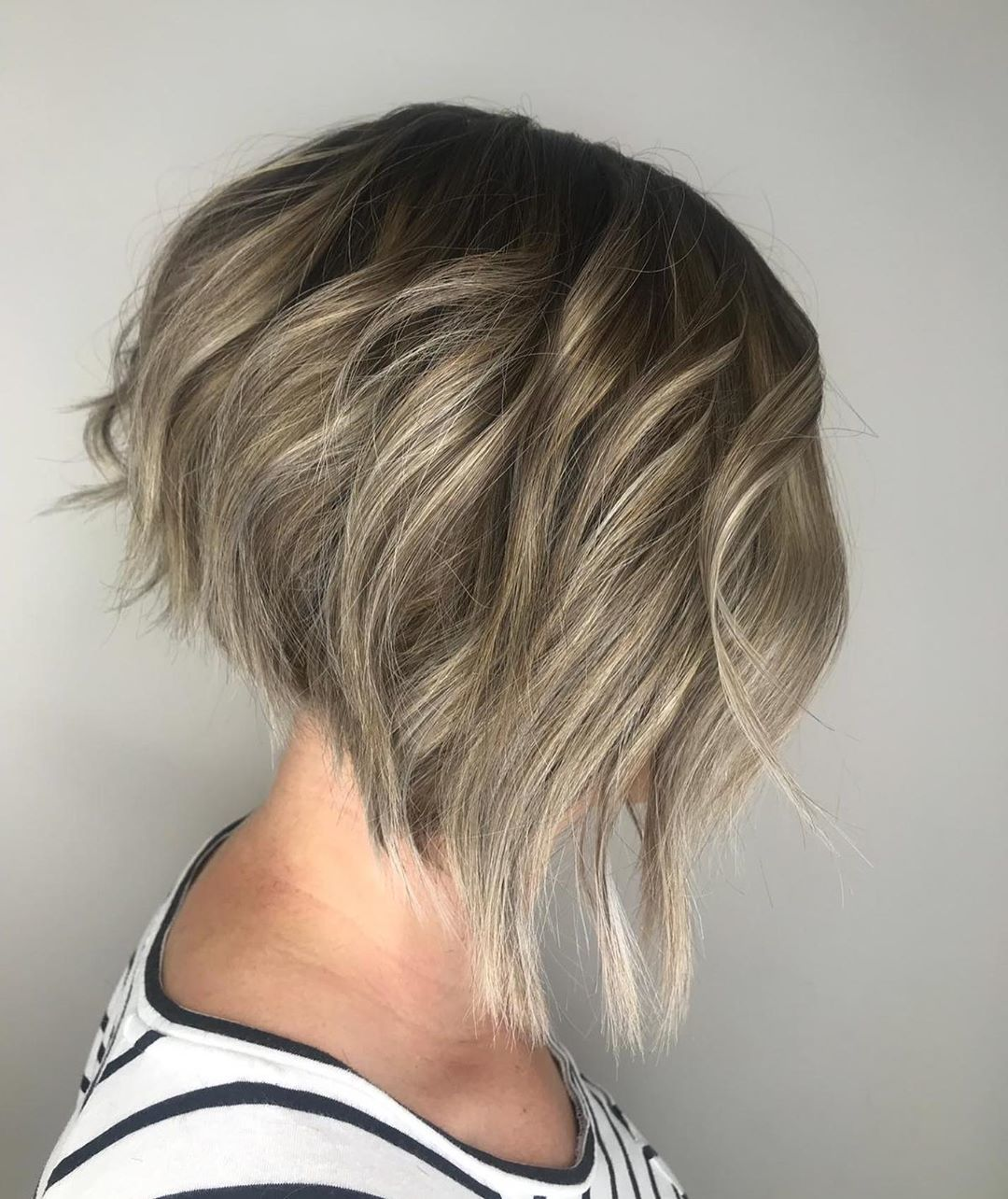 Woman with a dark blonde wavy graduated bob