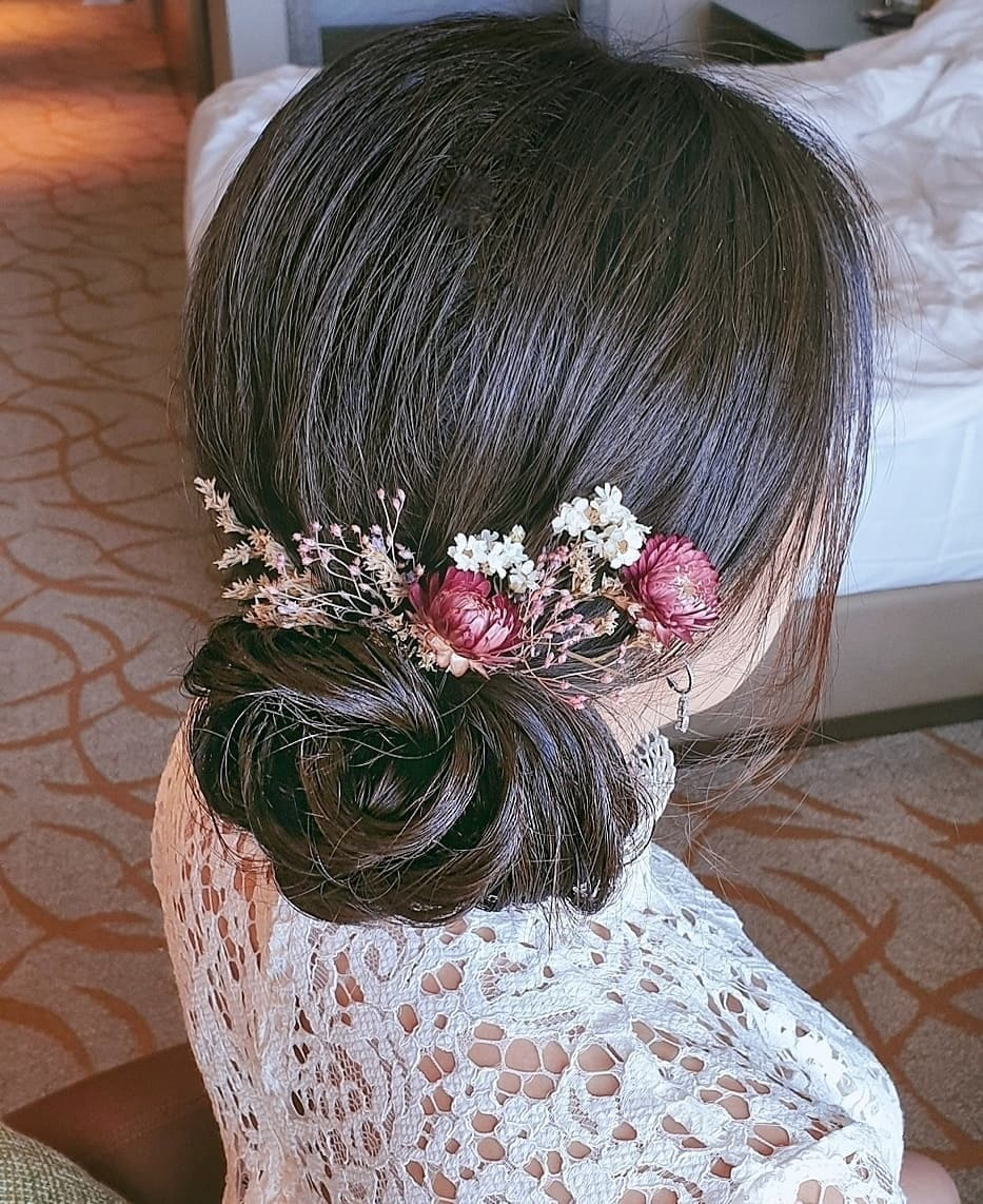 Woman with dark brown hair styled into a low textured side bun with flowers