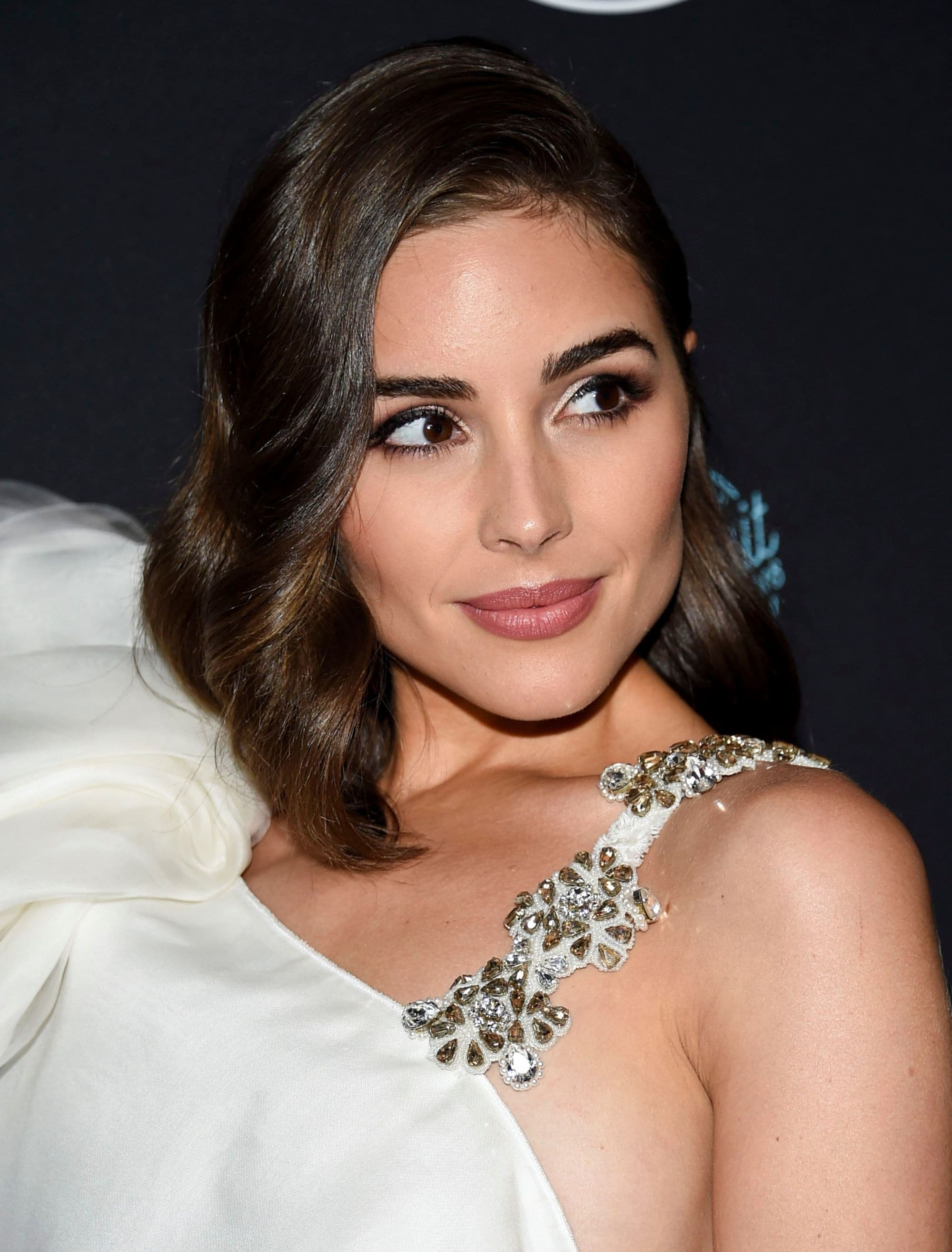 Olivia Culpo with side parted wavy brown bob